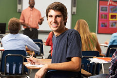 Male Teenage Pupil In Classroom. Sitting Down Smiling Stock Image