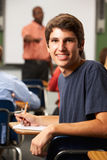 Male Teenage Pupil In Classroom. Sitting Down Smiling To Camera Royalty Free Stock Image