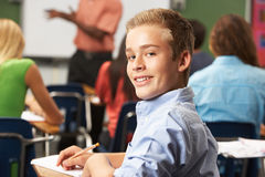 Male Teenage Pupil In Classroom. Smiling At Camera Sitting Down Stock Photography