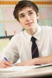 Male Teenage Student In Classroom. Male Teenage Student Studying In Classroom Royalty Free Stock Photo