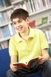 Male Teenage Student In Library Reading Book. Smiling Stock Image