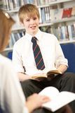Male Teenage Student In Library Reading Book Stock Photography