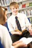 Male Teenage Student In Library Reading Book. Smiling Stock Images