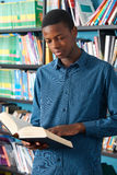 Male Teenage Student Reading Book In Library. Male Teenage Student Studies In Library Stock Images