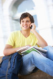 Male Teenage Student Sitting On College Steps. Male Teenage Student Sitting Outside On College Steps Using Mobile Phone Royalty Free Stock Photos