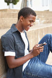 Male Teenage Student Sitting Outside. On College Steps Using Mobile Phone Royalty Free Stock Photo
