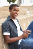 Male Teenage Student Sitting Outside. On College Steps Using Mobile Phone Stock Image