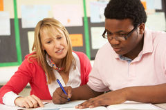 Male Teenage Student Studying In Classroom. Stock Photo