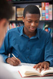 Male Teenage Student Working In Classroom. Male Teenage Student Works In Classroom Royalty Free Stock Photos