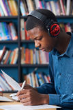 Male Teenage Student Working At Computer Wearing Headphones. Male Teenage Student Works At Computer Wearing Headphones Royalty Free Stock Photo