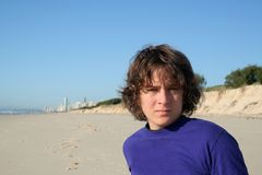 Male teenager on beach. Portrait of handsome male teenager on beach, blue sky background stock photo
