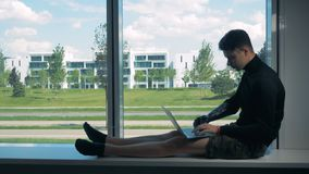 Male teenager with a bionic arm typing on a laptop. Futuristic human cyborg concept. Male teenager with a synthetic arm is sitting on a window sill and typing