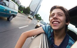 Male teenager in car enjoying city view Royalty Free Stock Image