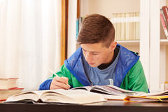 Male teenager concentrated doing homework. In a desk Royalty Free Stock Photo