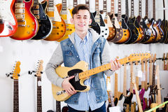 Male teenager examining electric guitars Stock Images