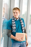 Male teenager holding book. Male teenager read book standing in modern glass building Royalty Free Stock Photo