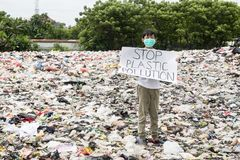 Male teenager holds stop plastic pollution text royalty free stock photos