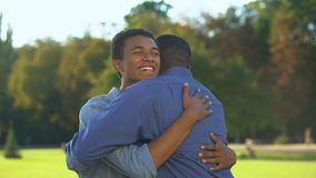 Male teenager hugging elder brother outdoors, family meeting happiness, love
