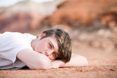 Male teenager laying on ground. Teenager male laying on the ground outdoors, natural light with mountains in background stock photos