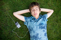 Boy listening to music on grass  Stock Photography