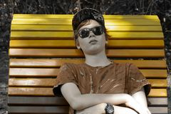 Male teenager lying on a colorful bench in orange royalty free stock photo