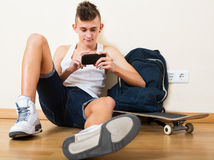 Male teenager playing with phone. Male teenager playing with the phone in domestic interior Royalty Free Stock Images