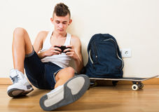 Male teenager playing with phone Royalty Free Stock Image