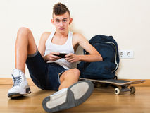 Male teenager playing with phone. Male teenager playing with a phone in the domestic interior Stock Images