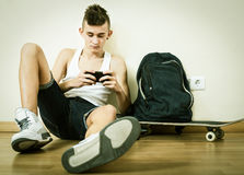 Male teenager playing with phone Stock Photo