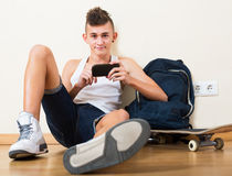 Male teenager playing with phone. Male teenager playing with the phone in the domestic interior Stock Photography