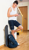 Male teenager playing with phone. In domestic interior at home Stock Photos