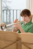 Male teenager playing the trumpet. Photo of a teenage male practicing his trumpet at home Stock Images