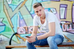 Male teenager with smartphone and earphones in urban city Stock Photos