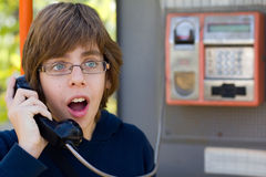 Male teenager talking on street phone. Young male teenager looking surprised while talking on a street phone Stock Photos