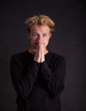 A male teenager thinking. With hands in front of his face Royalty Free Stock Photo