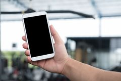male& x27; telefone celular da posse da mão de s no gym homem com o smartphone no ajuste Imagens de Stock Royalty Free