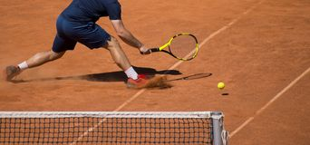 Male tennis player in action on the court on a sunny day.  Stock Photo