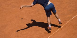 Male tennis player in action on the court on a sunny day.  Royalty Free Stock Photography
