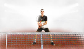 Male tennis player in action. Young man holding tennis racket and looking away while Royalty Free Stock Images