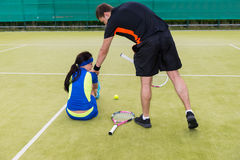 Male tennis player calms distressed female partner because of th. E loss who is sitting on the court  both wearing a sportswear outdoor in summer or spring Stock Images
