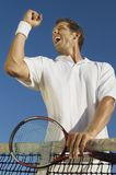 Male Tennis Player Celebrating Success. Low angle view of mid adult male tennis player celebrating success Royalty Free Stock Photography