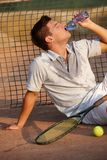 Male tennis player drinking water. Male tennis player sitting exhausted on hard court, drinking water Stock Images