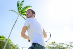 Male tennis player finishing serve playing outdoor. Man serve for game during outside tennis game. Fit male athlete living healthy fitness sport lifestyle Stock Photo