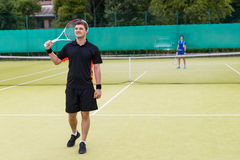 Male tennis player holding a racket on his shoulder after a matc Royalty Free Stock Images