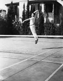 Male tennis player jumping for shot Stock Photos