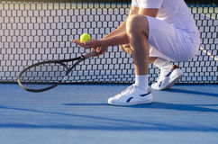Male tennis player kneeling beside net, no face. Male Caucasian athlete kneeling next to tennis net and holding tennis ball in his hand, no face Stock Photography