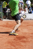 Male tennis player lunging for the ball. On his backhand and sliding on the loose surface of a clay court Stock Photo
