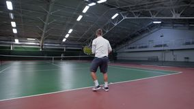 Male tennis player playing on indoor court against male player. He serving the ball. Sport leisure stock video