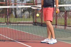 Male tennis player with racket ready to serve a tennis ball. Healthy fitness concept with active lifestyle Stock Photography