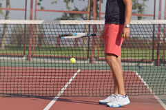 Male tennis player with racket ready to serve a tennis ball. Healthy fitness concept with active lifestyle Royalty Free Stock Image